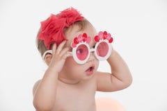 Ritratto di piccola neonata divertente in vetri divertenti del partito. fotografia stock libera da diritti