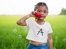 Ritratto di piccola ragazza asiatica che tiene cuore rosso Immagine Stock Libera da Diritti