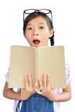 Ritratto di piccola ragazza asiatica che tiene un libro su bianco Fotografie Stock Libere da Diritti
