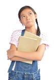 Ritratto di piccola ragazza asiatica che tiene un libro su bianco Fotografia Stock