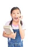 Ritratto di piccola ragazza asiatica che tiene un libro su bianco Fotografia Stock Libera da Diritti