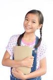 Ritratto di piccola ragazza asiatica che tiene un libro su bianco Immagine Stock