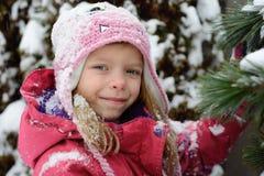 Ritratto di piccola ragazza bionda caucasica sul fondo dell'abete Immagine Stock Libera da Diritti