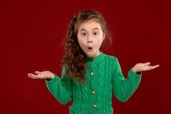 Ritratto di piccola ragazza castana con i capelli lunghi e ricci che posano contro un fondo rosso immagine stock libera da diritti