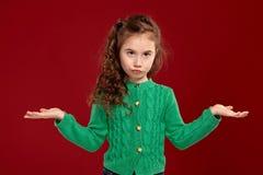 Ritratto di piccola ragazza castana con i capelli lunghi e ricci che posano contro un fondo rosso fotografia stock