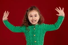 Ritratto di piccola ragazza castana con i capelli lunghi e ricci che posano contro un fondo rosso fotografia stock libera da diritti