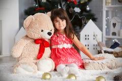Ritratto di piccola ragazza castana sveglia che abbraccia un grande orsacchiotto Immagine Stock