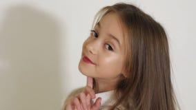 Ritratto di piccola ragazza dai capelli lunghi sveglia in studio, lei che posa per la macchina fotografica archivi video