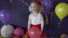 Ritratto di piccola ragazza sveglia che getta pallone rosso sulla sua festa di compleanno stock footage