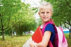 Ritratto di piccola scolara in un vestito blu dalla scuola, con la BO Fotografie Stock