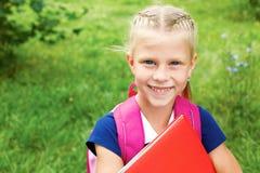 Ritratto di piccola scolara in un vestito blu dalla scuola, con la BO Immagini Stock