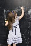 Ritratto di piccola scrittura sveglia della ragazza sulla lavagna Immagine Stock