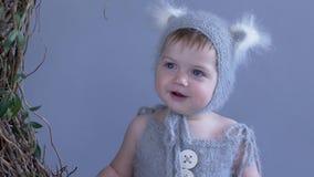 Ritratto di piccolo bambino con i grandi occhi azzurri in bello vestito con il cappuccio sul fondo blu della parete stock footage
