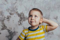 Ritratto di piccolo bambino sveglio premuroso con la mano che tocca fronte fotografia stock