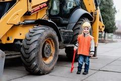 Ritratto di piccolo costruttore in elmetti protettivi che funzionano all'aperto vicino all'escavatore del trattore Immagini Stock Libere da Diritti