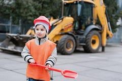 Ritratto di piccolo costruttore in elmetti protettivi che funzionano all'aperto vicino all'escavatore del trattore Fotografia Stock