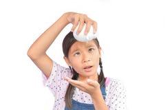 Ritratto di piccolo porcellino salvadanaio asiatico della tenuta della ragazza su bianco Fotografia Stock Libera da Diritti