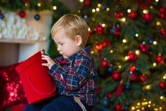 Ritratto di piccolo ragazzo biondo che si siede sul tetto in studio decorato e che gioca con i regali di Natale e le scatole Deco fotografia stock