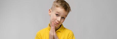 Ritratto di piccolo ragazzo caucasico biondo sveglio in maglietta gialla che spera chiedere il perdono su fondo grigio immagini stock libere da diritti