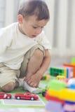 Ritratto di piccolo ragazzo caucasico che gioca con i giocattoli all'interno Fotografia Stock