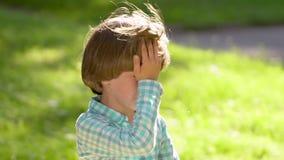 Ritratto di piccolo ragazzo triste biondo caucasico che grida e che esamina macchina fotografica con gli strappi Bambino del bamb stock footage