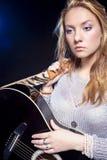 Ritratto di posa femminile bionda caucasica sembrante triste con la chitarra contro il nero Fotografie Stock Libere da Diritti
