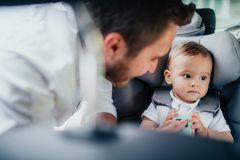 Ritratto di preoccuparsi giovane padre e neonato che godono del trasporto dell'automobile con il sedile del bambino fotografia stock