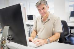 Ritratto di professore felice che lavora al computer fotografie stock libere da diritti