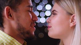 Ritratto di profilo del primo piano delle coppie multinazionali che guardano allegro negli occhi sul fondo vago delle luci stock footage