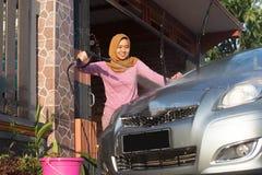 Ritratto di pulizia felice dell'automobile delle donne del hijab - rimuovendo il sapone con acqua, facendo uso di un tubo flessib immagine stock libera da diritti