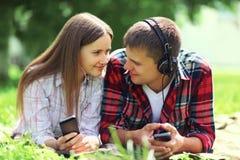 Ritratto di rilassamento di menzogne delle giovani coppie sull'erba insieme Fotografia Stock