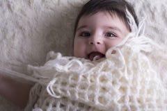 Ritratto di risata della neonata piccola sotto il panno tricottato Immagini Stock Libere da Diritti