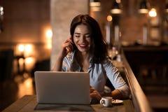 Ritratto di risata e della donna di affari bella che parlano sul telefono e che lavorano al suo computer portatile in ristorante  Immagine Stock Libera da Diritti