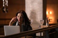 Ritratto di risata e della donna di affari bella che parlano sul telefono e che lavorano al suo computer portatile in ristorante  Fotografie Stock Libere da Diritti