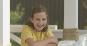 Ritratto di risata e sorridente di un adolescente che esamina macchina fotografica sul colpo bianco di Terrasse su rosso stock footage