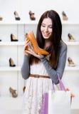Ritratto di ritratto a mezzo busto della donna che tiene scarpa tallonata Immagini Stock Libere da Diritti