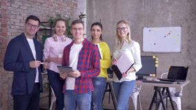 Ritratto di riuscito gruppo lavorante, del maschio sorridente di affari e delle donne durante le ore lavorative in ufficio archivi video