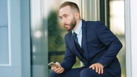 Ritratto di riuscito imprenditore dell'uomo d'affari che si siede con lo smartphone video d archivio