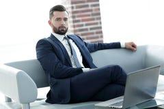 Ritratto di riuscito uomo d'affari che si siede nell'ingresso dell'ufficio Fotografie Stock Libere da Diritti