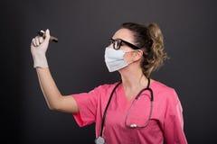 Ritratto di scrittura d'uso della maschera di medico attraente di signora con marzo Immagine Stock