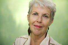 Ritratto di signora caucasica anziana che esamina e che sorride la macchina fotografica Fotografia Stock