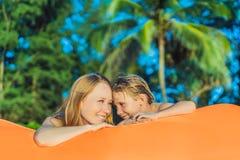 Ritratto di stile di vita di estate della madre e del figlio che si siedono sul sofà gonfiabile arancio sulla spiaggia dell'isola fotografia stock