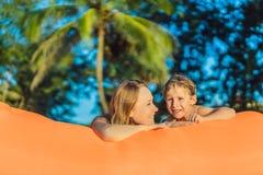 Ritratto di stile di vita di estate della madre e del figlio che si siedono sul sofà gonfiabile arancio sulla spiaggia dell'isola fotografie stock