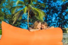Ritratto di stile di vita di estate della madre e del figlio che si siedono sul sofà gonfiabile arancio sulla spiaggia dell'isola fotografia stock libera da diritti
