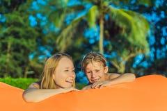 Ritratto di stile di vita di estate della madre e del figlio che si siedono sul sofà gonfiabile arancio sulla spiaggia dell'isola immagini stock