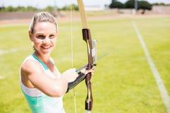 Ritratto di tiro con l'arco di pratica dell'atleta femminile Fotografia Stock