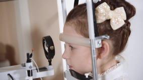 Ritratto di un adolescente che controlla la vista in una clinica del ` s dei bambini ad un medico stock footage