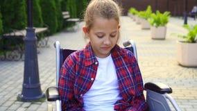Ritratto di un adolescente con un telefono in sua mano in una sedia a rotelle video d archivio