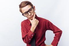 Ritratto di un adolescente positivo e flirt, su un fondo bianco, vetri, camicia rossa, tema di affari, pubblicità, immagini stock libere da diritti