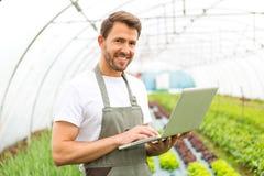 Ritratto di un agricoltore attraente in una serra facendo uso del computer portatile Immagini Stock Libere da Diritti